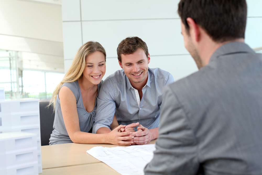 A happy couple holding hands and talking with their Mortgage Planner