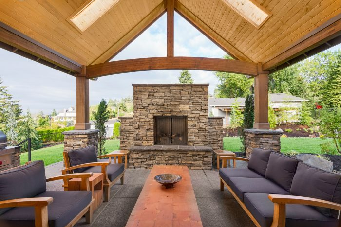a beautiful outdoor entertaining space equipped with furniture, a fireplace and more